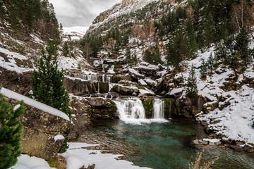 Cascada escalonada en un valle nevado