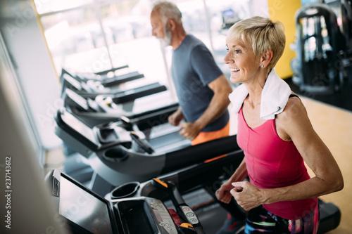 Starsi ludzie biega w maszynowym karuzeli przy sprawności fizycznej gym klubem