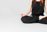 Young brunette slim woman in black sitting in Lotus position in yoga isolated on gray background