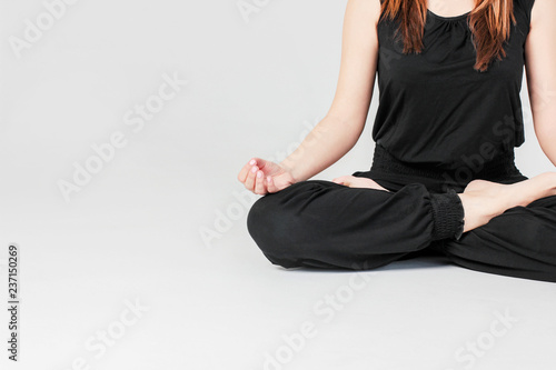 Naklejka Young brunette slim woman in black sitting in Lotus position in yoga isolated on gray background
