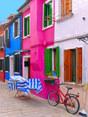 Burano, Italy. View of the colorful houses with windows, laundry cloths to dry outside and bicycle in the small picturesque island of Burano near