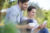 Relaxed young couple sitting together outside with mug and cellphone - 237162889