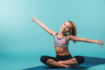 Happy little girl wearing sport clothing doing exercises © Drobot Dean