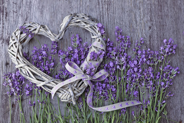 Lavender flowers with wicker heart on wooden background
