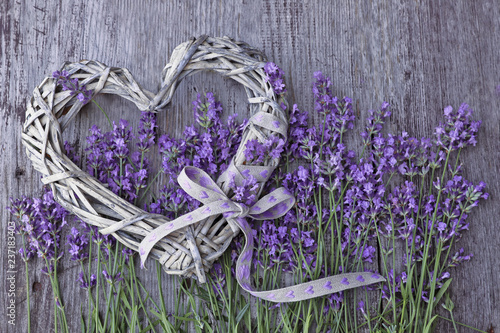 Lavender flowers  with wicker heart on wooden background  - 237183403
