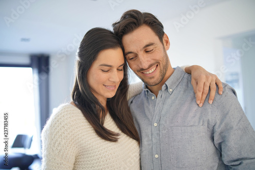 Portrait of gorgeous couple embracing at home - 237183455