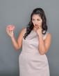 Leinwanddruck Bild - Plus size woman looking on donut with doubt. Overweight concept