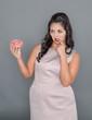 Leinwandbild Motiv Plus size woman looking on donut with doubt. Overweight concept