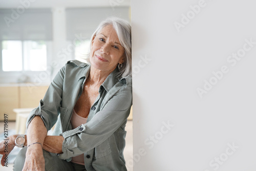 Beautiful relaxed elderly woman sitting at home