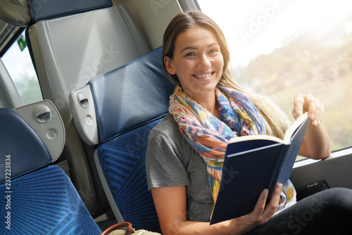 Relaxed young woman reading on the train