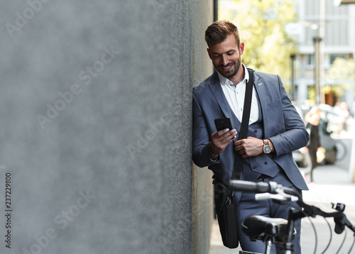 Portrait of young businessman with his bicycle looking at phone.