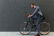 Smiling young businessman going to work with his bicycle, he's sitting on bike and looking at phone. - 237230014