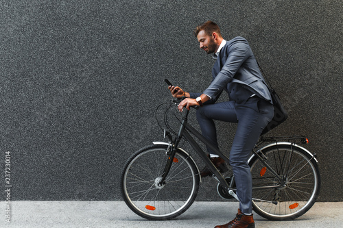 Smiling young businessman going to work with his bicycle, he's sitting on bike and looking at phone.