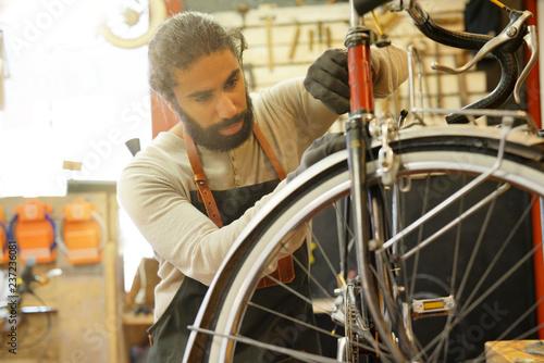 Man working in cycle repair shop