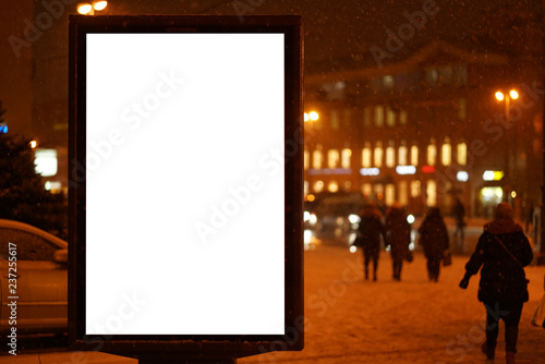 city outdoor billboard mockup winter city with snow going. Glows in the darkness of the night city.