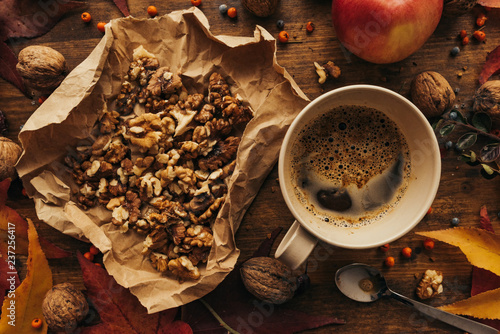 Enjoying fruits of autumn - apple, coffee and walnut on table - 237256417