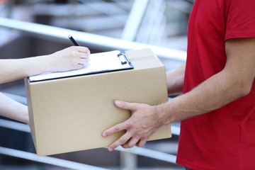 Delivery man in red uniform with cardboard box and clipboard