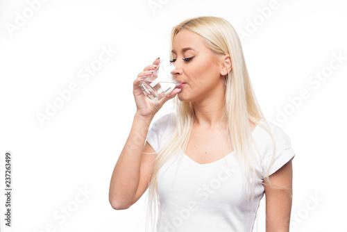 Zdrowy blond kobiety mienie i napój szkło woda na odosobnionym białym tle