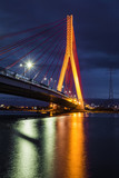 Illuminated cable stayed bridge over Martwa Wisla river at night in Gdansk. Poland Europe