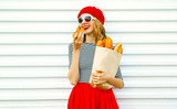 Portrait pretty woman eating croissant wearing red beret holding paper bag with long white bread baguette on white wall background