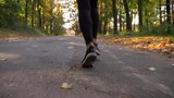 Dolly shot, from bottom to top, rear view of Muslim girl in hijab jogging in the autumnal forest - 237270405