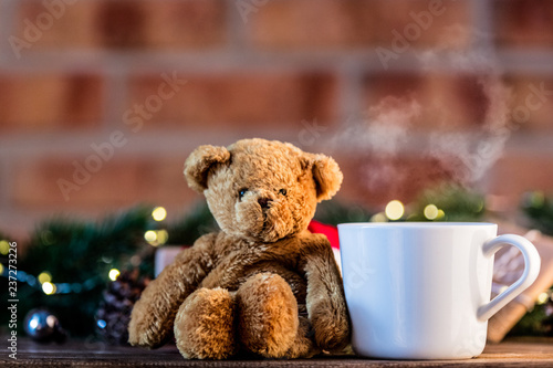 White Cup of tea near gift and Christmas Fairy Ligths at background - 237273226