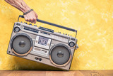 Retro outdated portable stereo boombox radio receiver with cassette recorder from circa 1980s in a strong man's hand front concrete textured yellow wall background. Vintage old style filtered photo
