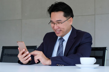 Asian businessman usiing smart phone at office background, business people on smart phone, business and technology