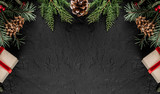 Creative layout frame made of Christmas tree branches, pine cones, gifts on dark background. Xmas and New Year theme, snow. Flat lay, top view, wide composition