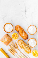 Farinaceous food. Fresh bread and raw pasta near flour in bowl and wheat ears on white stone background top view copy space