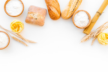 Products made of wheat flour. White flour in bowl, wheat ears, fresh bread and raw pasta on white background top view space for text
