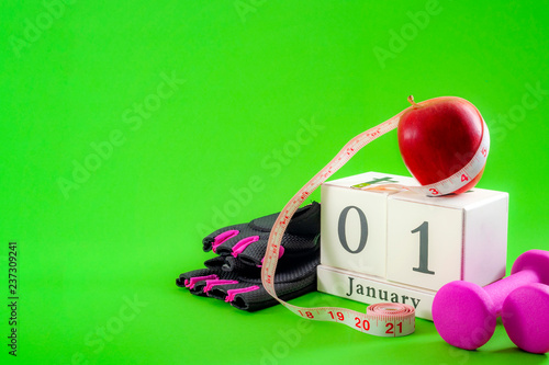 Leinwanddruck Bild New year resolution and start a diet concept with an apple, pink dumbbells and gym gloves next to a cube calendar showing the date of january 1st on bright vivid green background with copy space