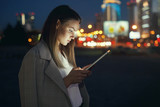 Beautiful woman with tablet outside in the night city - 237315861