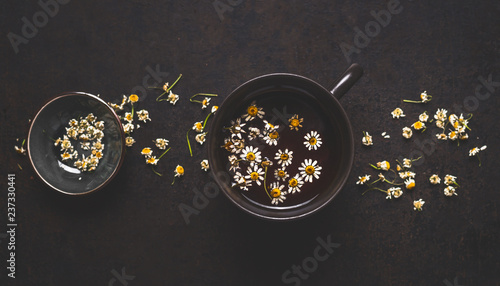 Foto Murales Healthy chamomile tea on dark background, top view. Herbal medicine and  medicinal herbs concept.