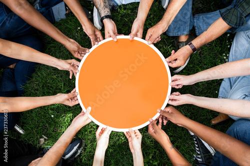 Leinwanddruck Bild Group of people holding a round orange board