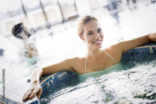 Leinwandbild Motiv Portrait of beautiful woman relaxing in swimming pool