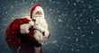 Santa Claus holding a bag with presents and ringing a bell on a dark background with snow  - 237344409