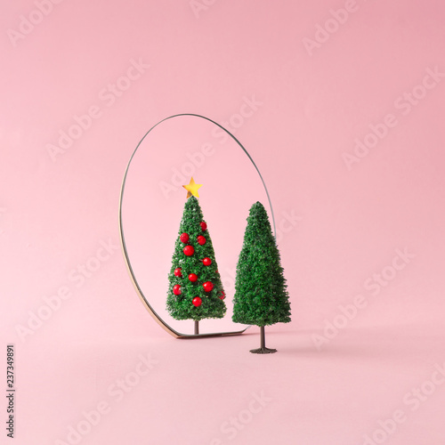 Christmas tree with mirror on pastel pink background. Minimal New Year decoration concept.
