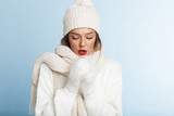 Frozen young woman wearing sweater and hat