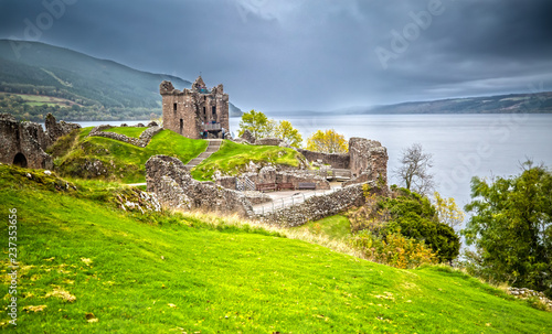 Leinwanddruck Bild Urquhart Castle with Dark Cloud Sky and Loch Ness in the Background
