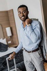 smiling african american businessman with gray jacket and travel bag in hotel room