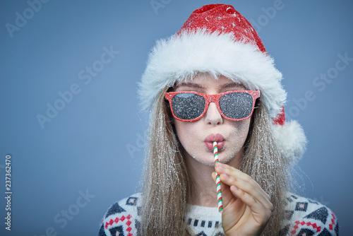 Leinwanddruck Bild Frozen girl with snow on face wearing Santa hat and sunglasses