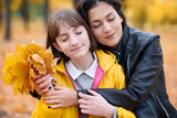 Pretty woman and teen girl are posing with bunch of maple's leaves in autumn park. They are closing eyes and dreaming. Beautiful landscape at fall season. - 237366014