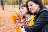 Pretty woman and teen girl are posing with bunch of maple's leaves in autumn park. They are closing eyes and dreaming. Beautiful landscape at fall season. - 237366058