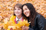 Pretty woman and teen girl are posing with bunch of maple's leaves in autumn park. Beautiful landscape at fall season. - 237366094