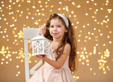 girl child is posing with lantern in christmas lights, yellow background, pink dress - 237366434