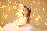 girl child is playing with christmas lights, yellow background, pink dress - 237366461