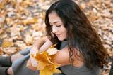 Pretty woman is sitting in autumn park near big tree. Beautiful landscape at fall season. - 237366899