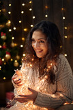 young girl is in christmas lights and decoration, dressed in white, fir tree on dark wooden background, winter holiday concept - 237367085