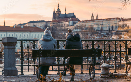 obraz lub plakat Two women sit on old wooden bench. An astonishing view of the colorful Prague gothic Castle over the Vltava River with Charles Bridge at Sunset. December 2018. Vintage photo effect bench